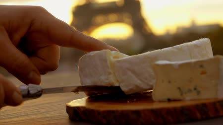 пармезан : Hand takes a piece of a soft brie cheese from a wooden board on the background of the Eiffel Tower, Paris, France