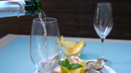 osztriga : Champagne is poured into a glass on the background of the plate with lemon and fresh oysters