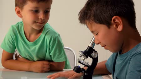 científico : Two cute tanned sibling boys look through a microscope