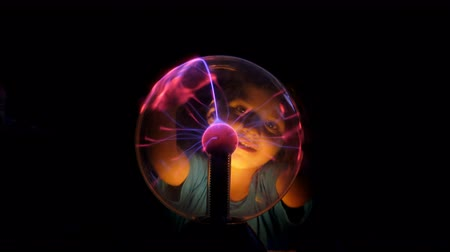 geheimnisvoll : Little boy examines the Tesla lamp. He touches the Tesla lamp with his fingers, smiles