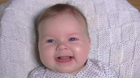baby chubby : Cute adorable baby laying on a white blanket and smiling happily at the camera