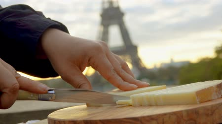 пармезан : Hand slicing hard goat cheese on a wooden board with knife on the backdrop of the Eiffel Tower, Paris, France