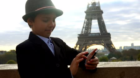 フランス : Teenage boy in a hat is looking the images on the phone on the background of the Eiffel tower, Paris, France