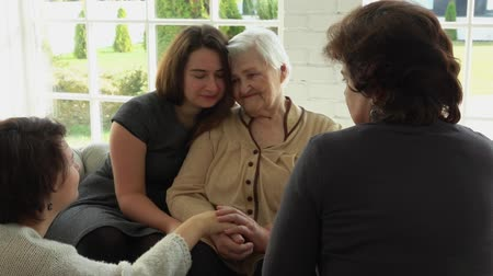 elderly care : Elderly white-haired woman is sitting on the sofa with her daughter and granddaughters. The beautiful multi-generations family enjoys togetherness Stock Footage