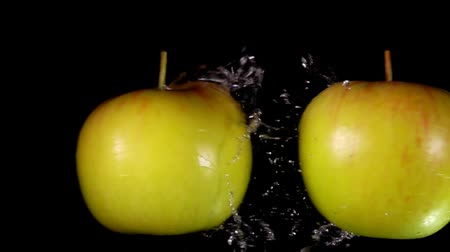 bounce : Water splashes beautifully scatter away from two red-green apples colliding together on a black background Stock Footage