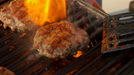 poivre noir : Beef cutlet is pressed to the grill with a black kitchen spatula. Flames on the background Vidéos Libres De Droits