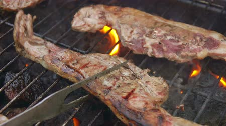 pişmemiş : Pieces of half-prepared meat steak are flipped on the grill with flames Stok Video