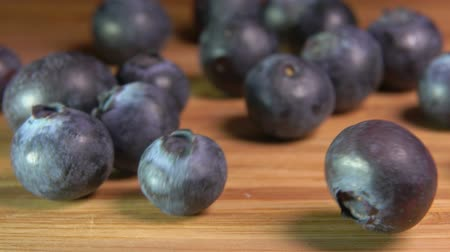 c vitamini : Large mouth-watering ripe blueberries fall on a wooden surface of a table