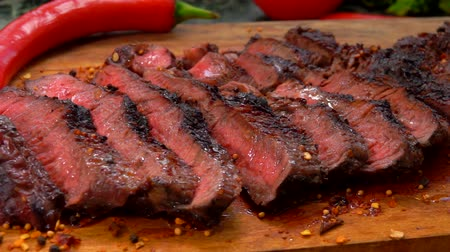 açougue : Slices of prepared meat steak sprinkled with pepper and spices lay on the wooden board