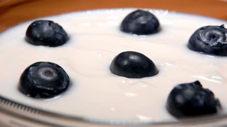 malina : Big juicy blueberries fall on delicious yogurt. Healthy breakfast