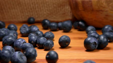 vitamine c : Big mouth-watering ripe blueberries roll on a wooden surface of a table against a burlap background