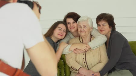 atirar : Photographer is taking pictures of an elderly white-haired woman with her granddaughters. The multi-generations family enjoys togetherness
