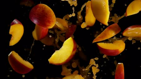 rodajas de naranja : Slices of peaches are flying and rotating with splashes of juice on the black background in slow motion