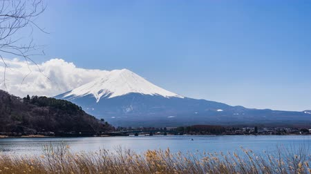 vulkán : Beautiful scenery View of Mount Fuji at kawaguchiko, Japan in the sunny day with moving cloud, Lake kawaguchi is a very popular for tourists and photographers Stock mozgókép