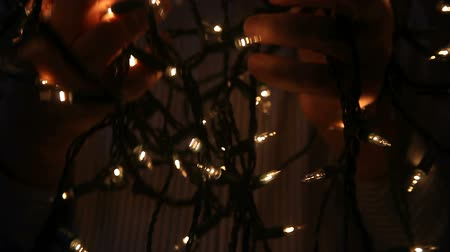 emaranhado : a man tries to unravel strings of Christmas lights