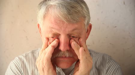 dörzsölés : an older man tries to relieve the pain around his eyes