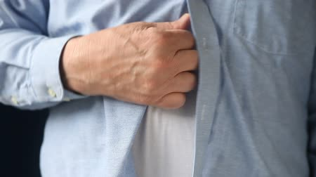 undershirt : a businessman scratches a persistent itch on his torso
