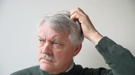 itch : senior man scratches his head either due to a scalp irritation or because he is confused