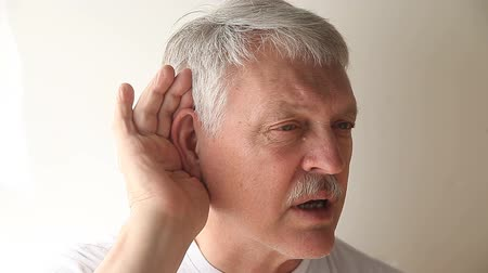 incapacidade : an older man strains to hear what someone is saying