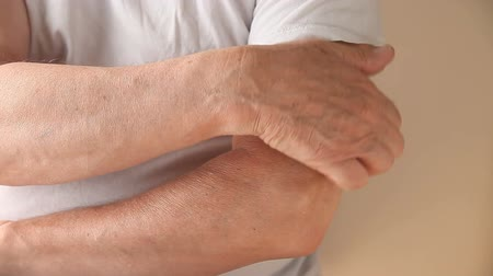 itch : a man scratches a persistent itch on his arm Stock Footage