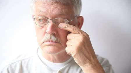 протирать : senior man takes off his glasses to rub his very tired eyes