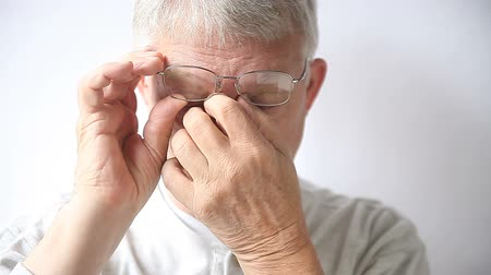 irritáció : an older man rubs the area affected by his glasses