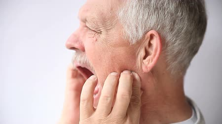 челюсти : an older man experiencing pain either in his teeth or jaw joint