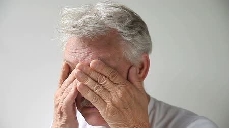 masaż twarzy : fatigued older man rubs his eyes