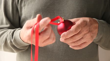 ügyesség : a man ties a red ribbon on an ornament
