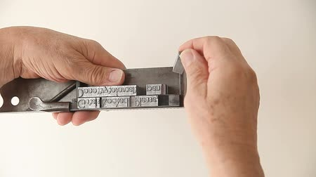 text knihy : a man makes adjustments to blocks of metal type in his composing stick tool