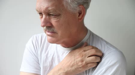 undershirt : an older man with a persistent itch on his shoulder