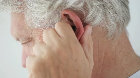 masaż twarzy : Senior man rubs his ear to relieve discomfort.