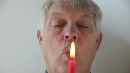respiração : Senior man fails to extinguish candle flame due to shortness of breath