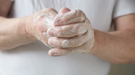 mydło : A man works soapy lather into his hands.