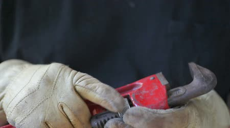 hydraulik : A man checks his wrench while wearing work gloves