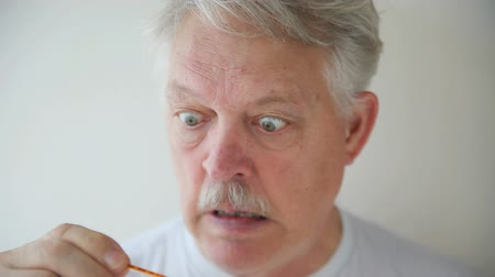 pára choque : A feverish older man is startled to see his temperature. Stock Footage