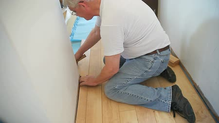 ajoelhado : A man kneels as he puts in laminate floor boards. Vídeos