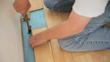 ajoelhado : A man installs a laminate floor in his home.