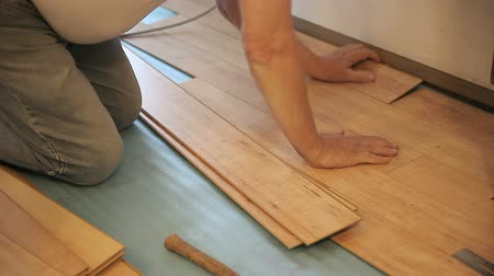 ajoelhado : A man fitting laminate boards in his house.