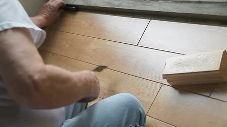 martelo : Man uses various tools to lock laminate flooring in place. Stock Footage