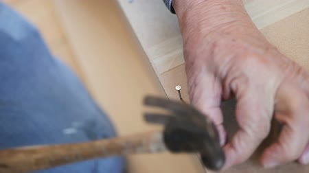 martelo : A man hammers nails onto a bookcase piece.