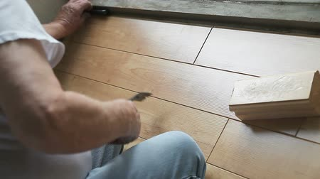 ajoelhado : A man fitting laminate flooring by a window