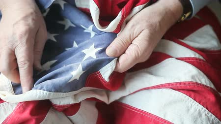 veterano : Senior man examines details of a vintage fabric flag Stock Footage
