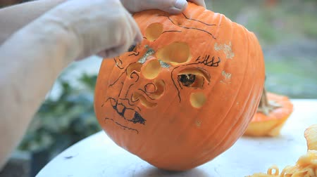 roliço : Man carving a jack o lantern face in his backyard. Stock Footage