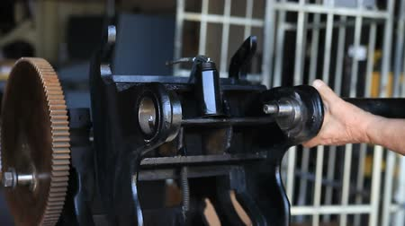 eixo : A printer puts together a vintage cast iron letterpress machine. Stock Footage