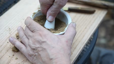 mashing : A man grinds oak galls to a powder to use as ink pigment. Stock Footage