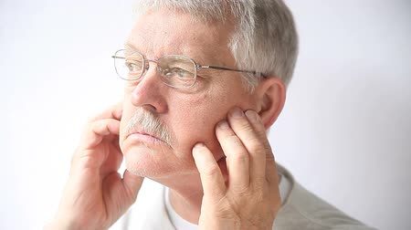 mračící : Closeup of older man who indicates where he feels pain near his cheekbones