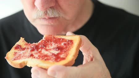 vaj : A senior man eating a slice of toast spread with butter and jam