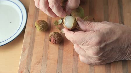 lychees : Senior man pulls off outer covering of a fresh lychee Stock Footage