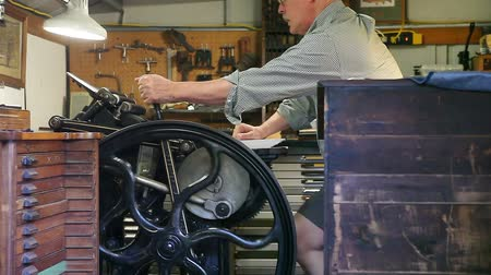 text knihy : man prints out cards on an antique press in his studio